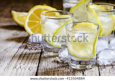 Lemon vodka with ice, vintage wooden background, selective focus - stock photo
