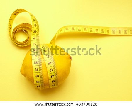 lemon with a measuring tape on a yellow background