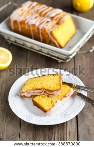 Lemon yogurt loaf cake, sliced on a creative plate on wooden background for your design - stock photo