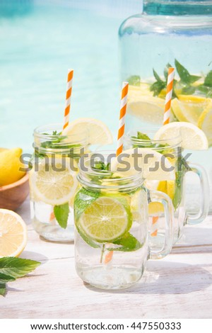 Lemonade drink in the jug on the white table near the pool