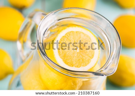 Lemonade. Fresh lemons in the jar.  Shallow depth of field. - stock photo
