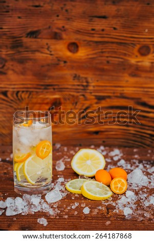 Lemonade in a glass with ice. On a wooden background. Sliced lemon and fortunella - stock photo