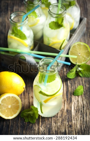 Lemonade in glass bottle with ice and mint - stock photo