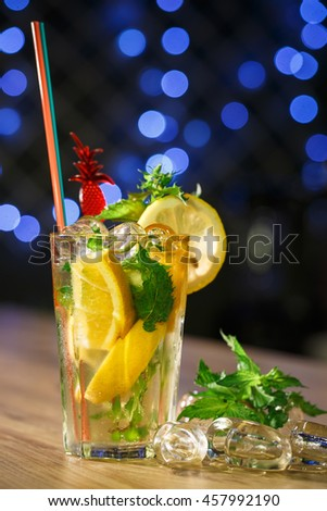 Lemonade in glass with fresh lemon on wooden table