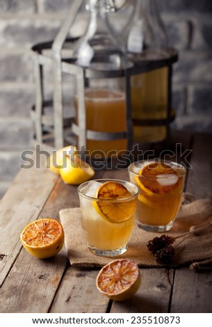 Lemonade in glasses and bottles made of grilled lemons on a wooden background.