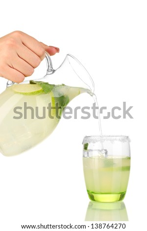 Lemonade in pitcher and glass isolated on white