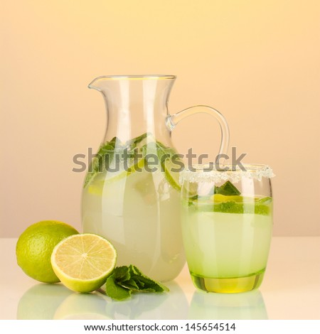 Lemonade in pitcher and glass on yellow background