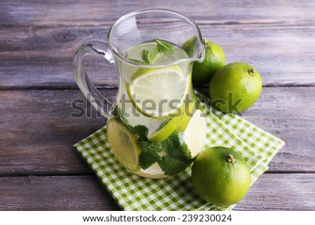 Lemonade in pitcher on wooden background - stock photo