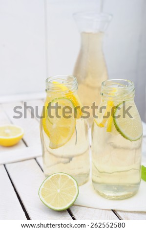 Lemonade in the jug and glasses with lemons and lime on white rustic table - stock photo
