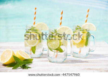 Lemonade in the jug and lemons with mint on the table outdoor near the pool