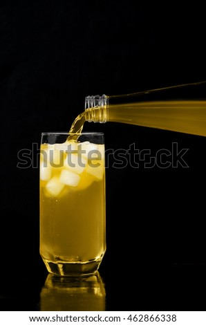 Lemonade is poured into the glass, on a black background