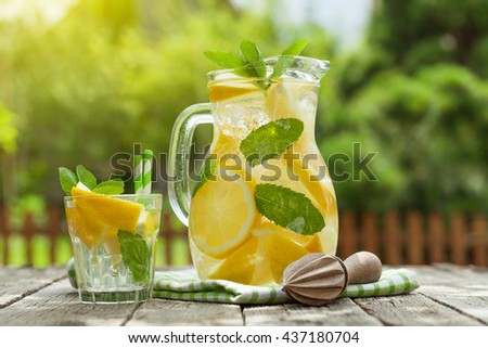 Lemonade pitcher and glass with lemon, mint and ice on garden table - stock photo