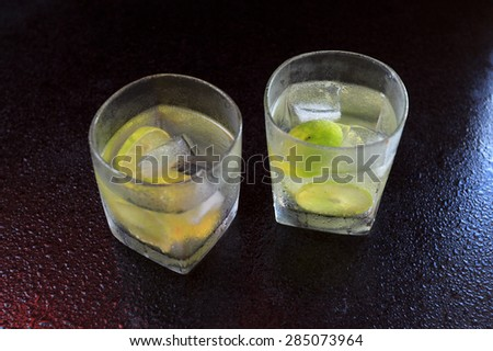 Lemonade served on a dark marble bar top garnished with a lime view 2 - stock photo