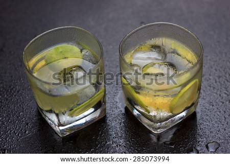 Lemonade served on a dark marble bar top garnished with a lime view 3 - stock photo