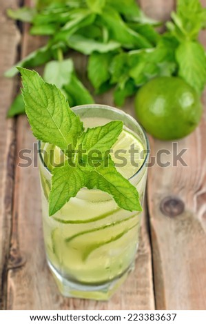Lemonade with fresh cucumber, lime and mint in glass, close up view