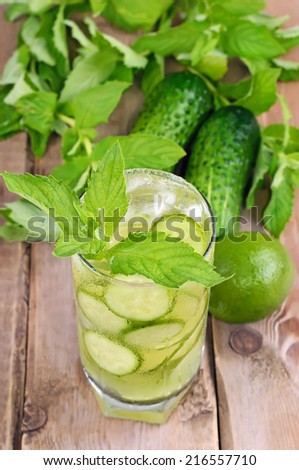 Lemonade with fresh cucumber, lime and mint in glass on rustic table
