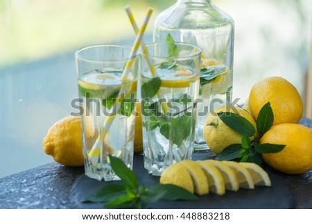 Lemonade with fresh lemon and mint by lemon  - stock photo