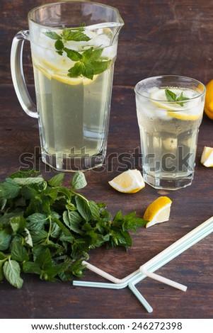 Lemonade with fresh lemon and mint on wooden background - stock photo