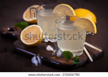 Lemonade with fresh lemon and mint on wooden background - stock photo