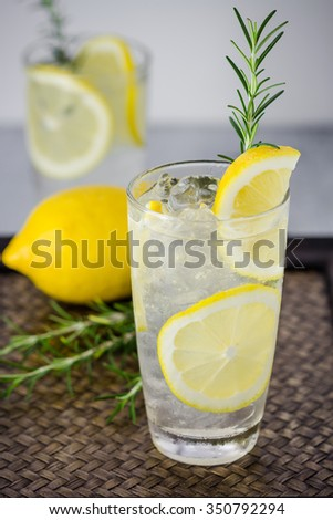 Lemonade with fresh lemon and rosemary in glass on wooden background - stock photo