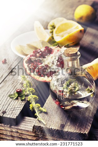 Lemonade with fresh lemon, mint and pomegranate on wooden background, fruits and drinks