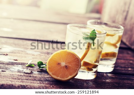 Lemonade with fresh lemon on wooden background - stock photo