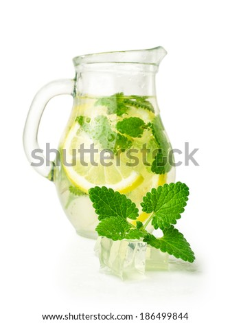 lemonade with ice and mint in a glass jug isolated on white - stock photo