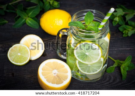 Lemonade with mint in a mason jar on old wooden background. Summer drink. - stock photo