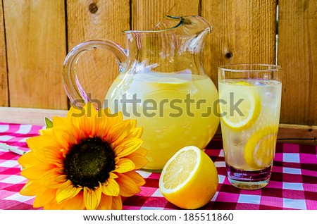 Lemonade with sliced lemons, pitcher, and sunflower on gingham table cloth. - stock photo