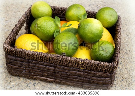 Lemons and limes in brown wooden basket, weight loss vegan diet food  - stock photo