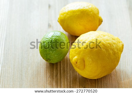 Lemons and limes with mint leaves on a wooden cutting board