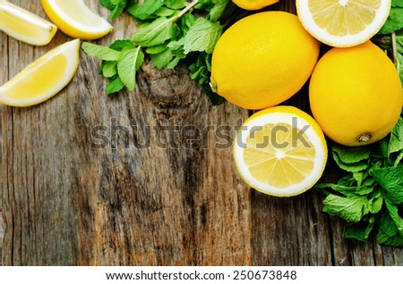 lemons and mint on a dark wood background. tinting. selective focus - stock photo