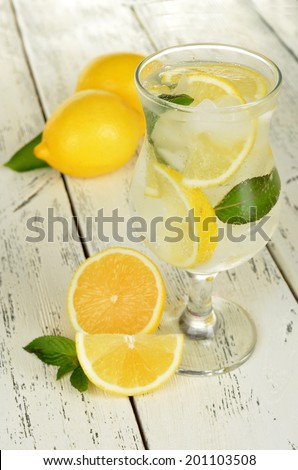Lemons in a glass with water on white wooden background