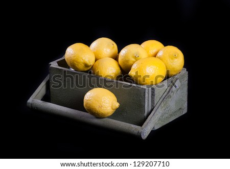 Lemons in the wood box, isolated on black. - stock photo