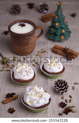 Lemons mini muffins with cream, lemon peel and silver sugar balls with cup of hot milk with cardamom, anise and cinnamon sticks with Christmas tree candle - stock photo