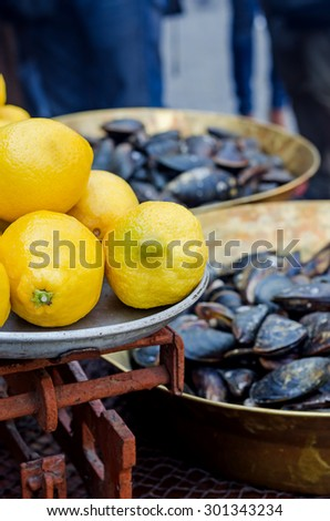 lemons rustic iron scales on a background of fresh mussels - stock photo