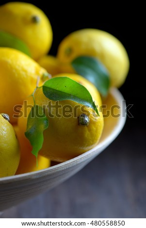 lemons with leaves on an old wooden table
