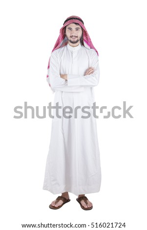 Length full of of arabic person with muslim clothes standing in the studio while folded his arms, isolated on white background