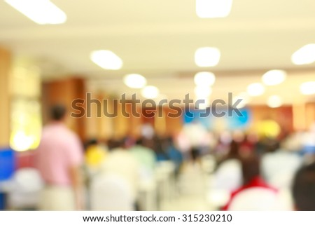 Lens blur on crowd sitting in convention room - stock photo
