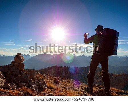Lens flare light, strong defect. Tourist guide on Alps peak takes photo. Strong hiker with big backpack  Alpine mountain. Alone man on few days trek