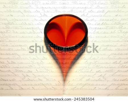 Lens making a heart shape on a book - stock photo