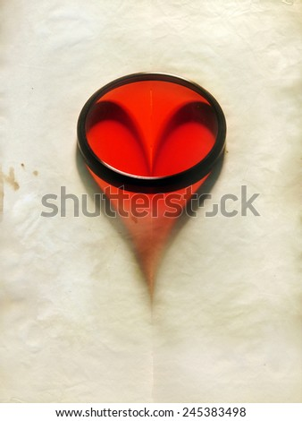 Lens making a heart shape on an old paper sheet     - stock photo