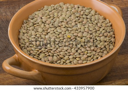 Lentil in bowl on wooden table - stock photo