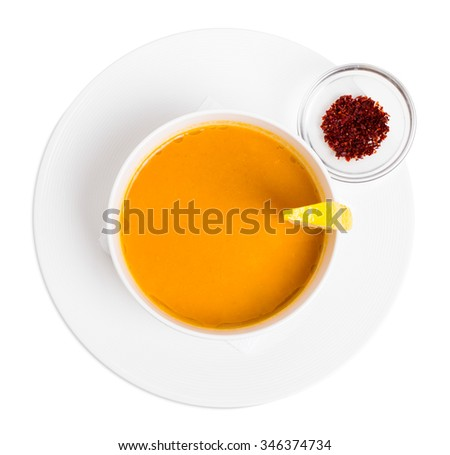 Lentil soup cream with lemon slice and dried minced paprika spice. Isolated on a white background. - stock photo