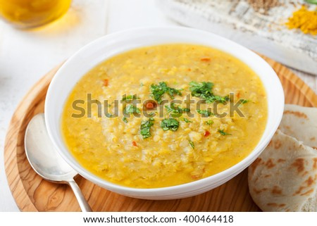 Lentil soup with pita bread in a ceramic white bowl on a wooden background - stock photo