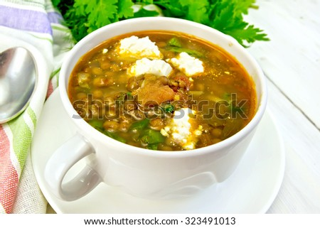 Lentil soup with spinach, tomatoes and feta cheese, napkin, spoon, parsley on a light wooden board