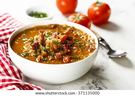 Lentil soup with tomatoes and sausages - stock photo