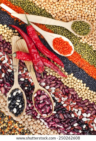 lentils, beans, peas, soybeans, legumes with spoons, textured background, top view - stock photo