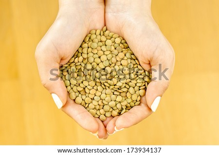 Lentils in woman's hands on beige background