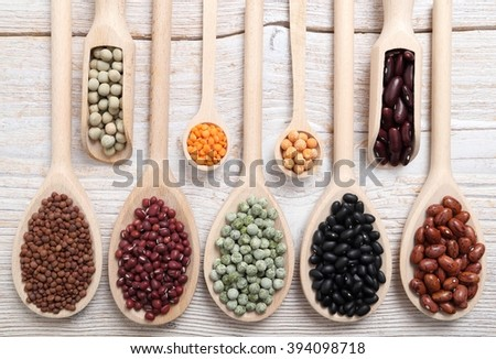 Lentils, peas and beans on wooden spoons. - stock photo